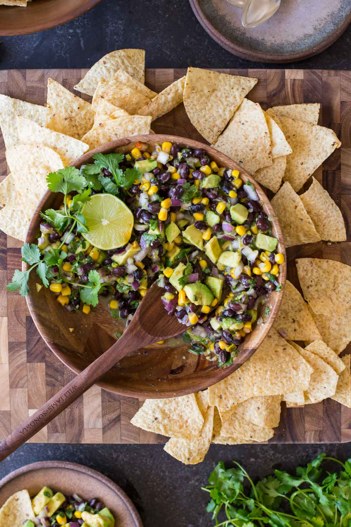 Quick and easy Avocado Dip in a bowl surrounded by tortilla chips.
