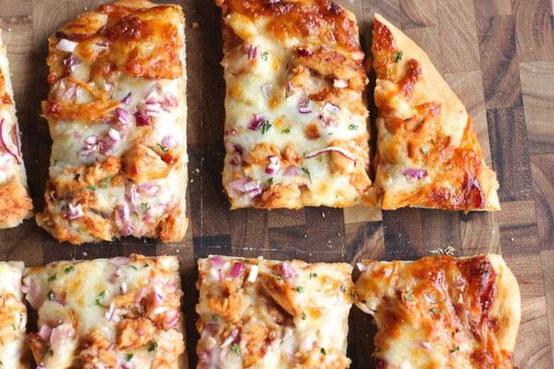 BBQ Chicken Pizza sliced on a cutting board.