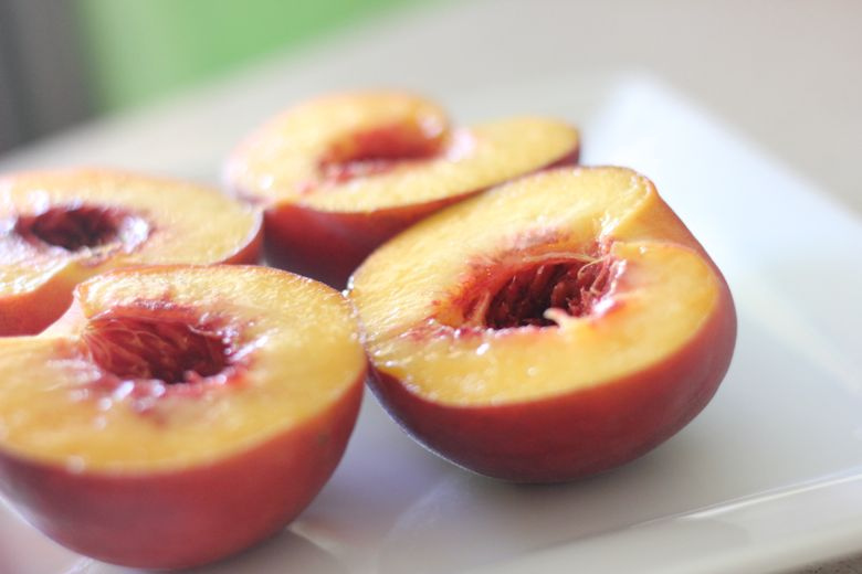 Peaches sliced in half and pit removed on a plate.