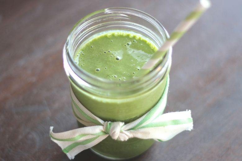 Green Smoothie in a glass jar with a drinking straw.