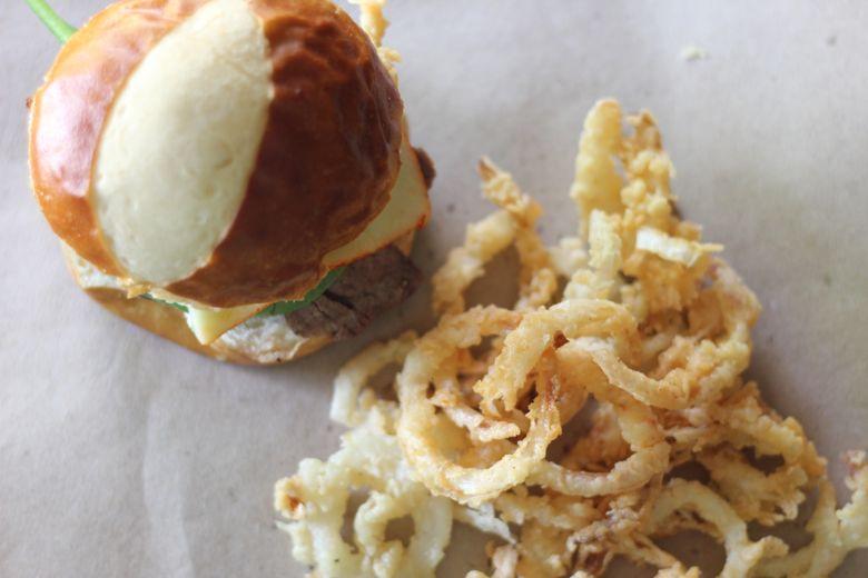 Steak Sandwich with Onion Straws next to it.