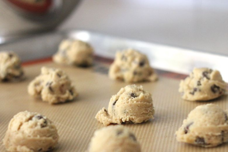 Emilee's Chocolate Chip Cookie dough scoops on a Silpat lined baking sheet.