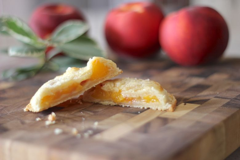 Peach Hand Pie cut in half on a cutting board with whole peaches in the background.