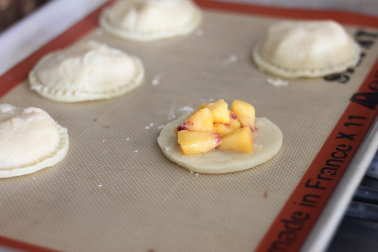 Peach Hand Pies on a Silpat lined baking sheet before baking.
