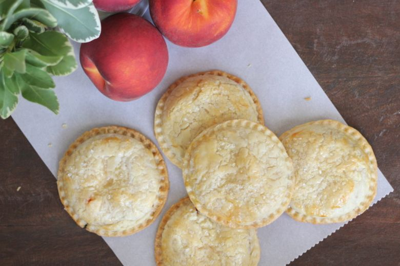 Peach Hand Pies on parchment paper next to whole peaches.