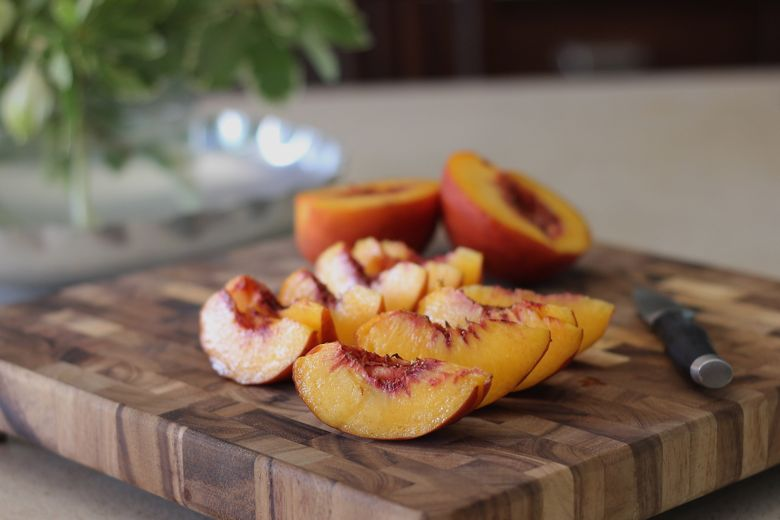 Sliced peaches on a cutting board.