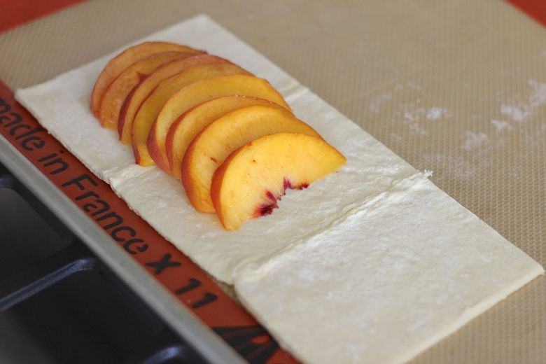 Peach slices arranged on puff pastry on Silpat lined baking sheet.