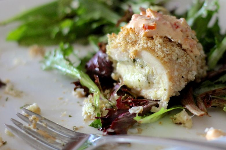 Pesto Stuffed Chicken With Sun-Dried Tomato Cream over greens on a plate.