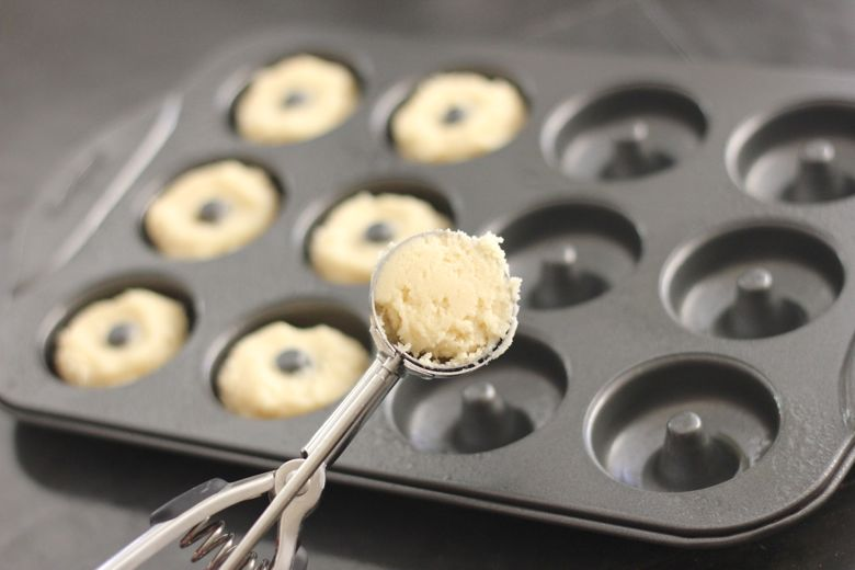 Sugar Cookie Donut dough in a cookie scoop with donut mold in the background.