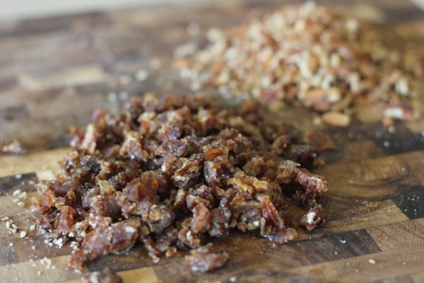 Chopped dates and chopped pecans on a cutting board.