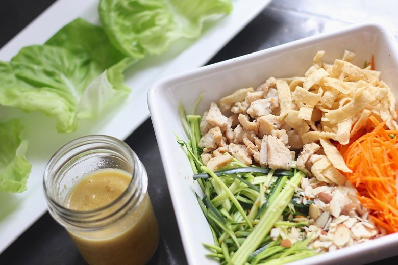 Asian Chicken Veggie Wrap filling ingredients in a large bowl with a jar of dressing and a plate of butter lettuce leaves.