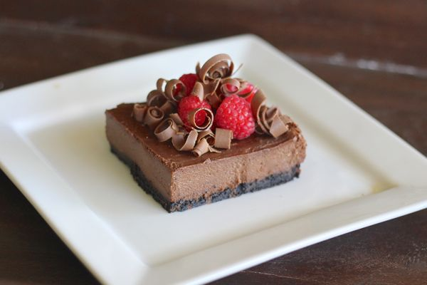 Chocolate Cheesecake with Raspberries on a plate.