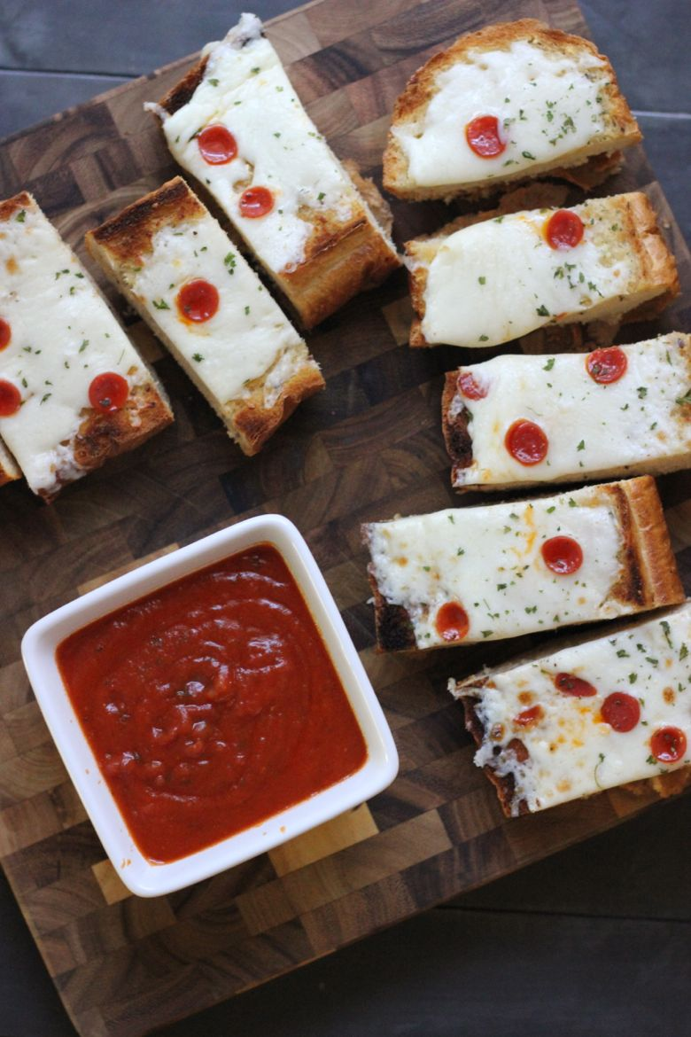 Whole Wheat Garlic Bread Pizza sliced on a cutting board with marinara in a cup.