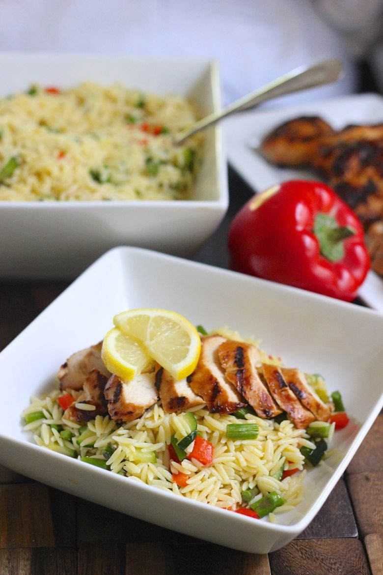 Lemon Garlic Orzo With Roasted Vegetables and sliced grilled chicken on top in a bowl.