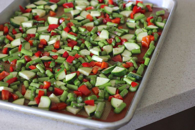 Chopped zucchini, red peppers and asparagus on a baking sheet.