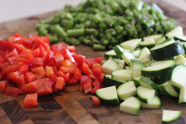Chopped zucchini, red peppers and asparagus on a cutting board.