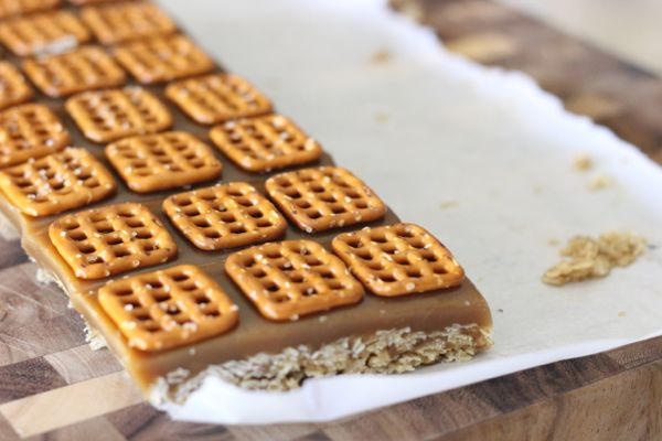 Salted Caramel Oat Bars on parchment paper on a cutting board.