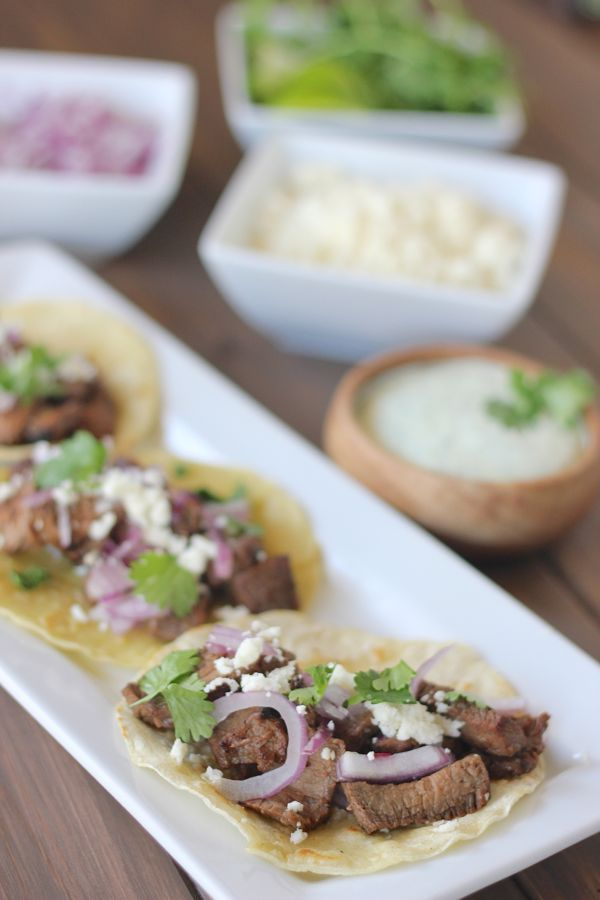 Grilled steak, red onions, and queso fresco on a lightly fried white corn tortilla.
