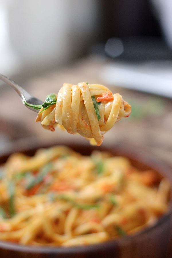 Creamy Roasted Red Pepper and Spinach Linguine twirled onto a fork.