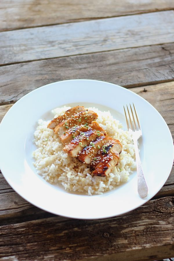 Homemade Teriyaki Chicken sliced and served over rice on a plate with a fork.