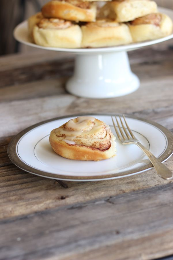 Maple Glazed Cinnamon Roll on a plate with a fork.