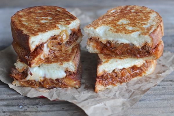 Two Sloppy Joe Paninis With Baby Swiss and Caramelized Onions cut in half and stacked next to each other.