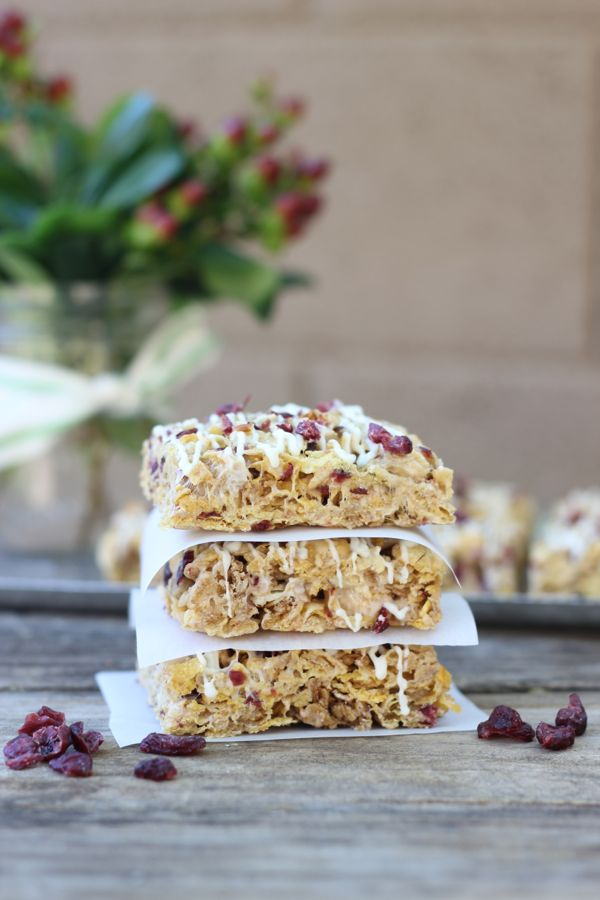 Cranberry Almond Brown Butter Cereal Bars cut into squares and stacked three high with parchment paper in between.