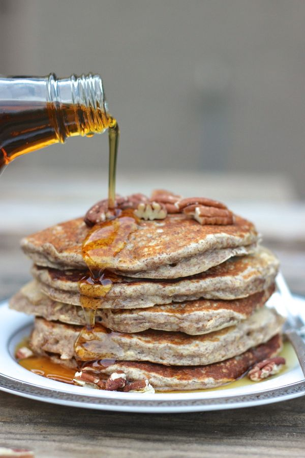Healthy Pumpkin Pie Spice Oatmeal Flax Pancakes stacked and topped with pecans and maple syrup being poured over it.