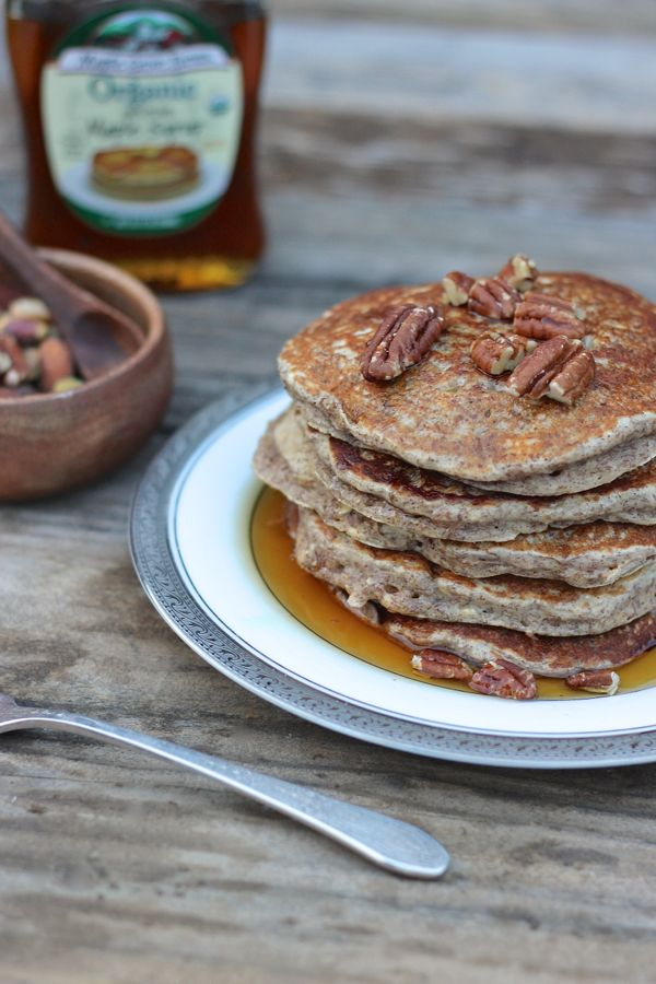Healthy Pumpkin Pie Spice Oatmeal Flax Pancakes stacked and topped with pecans and maple syrup.
