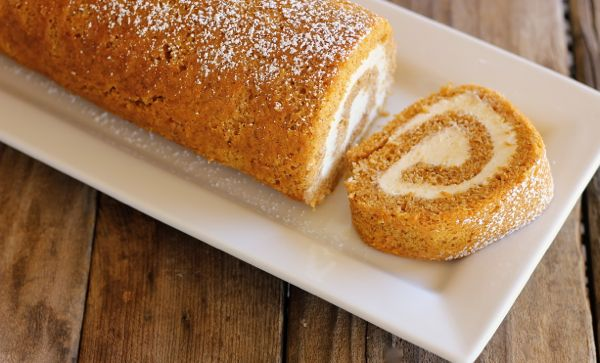 Pumpkin Roll With Maple Cream Cheese Filling on a serving plate with one piece sliced off the end.