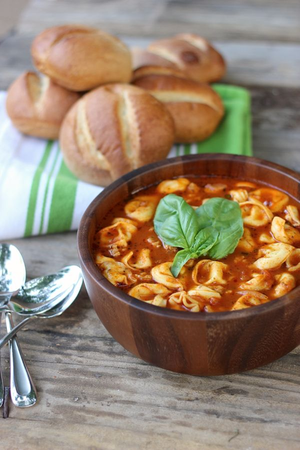 Easy Tomato Basil Soup With Chicken Sausage and Cheese Tortellini in a bowl with garnish on top and dinner rolls in the background.