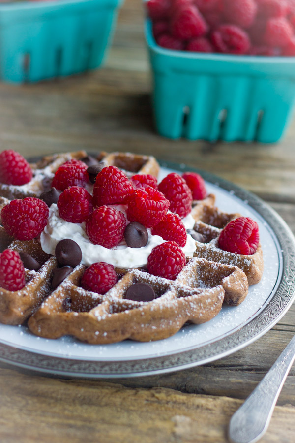 Chocolate Waffles With Fresh Raspberries, topped also with whipped cream and chocolate chips on a plate, with cartons of fresh berries in the background.