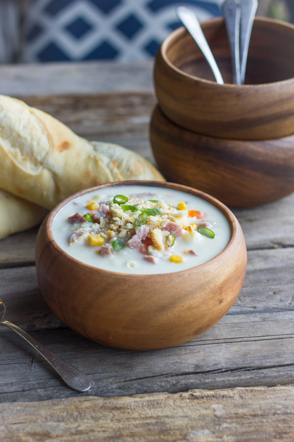 Creamy Potato Soup With Ham in a bowl, with loaves of bread and bowls in the background.