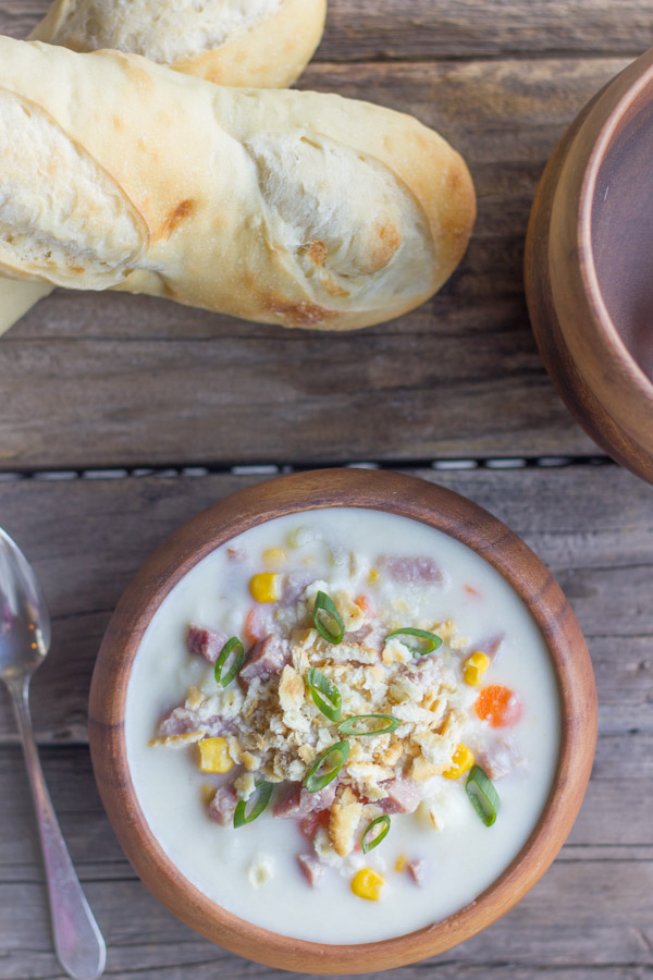Creamy Potato Soup With Ham in a bowl with loaves of bread next to it.