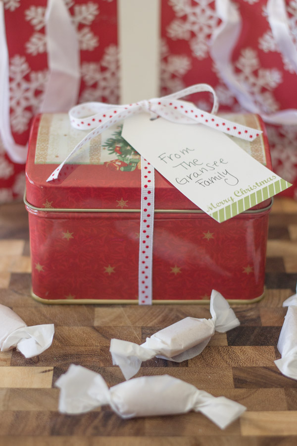 Homemade Soft Caramels wrapped in parchment paper in front of a Christmas tin.