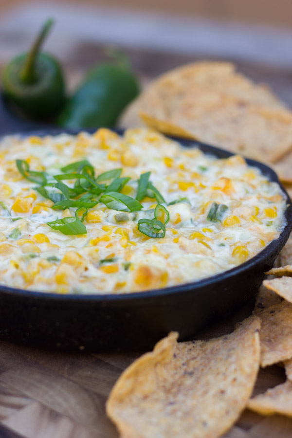 Hot Jalapeño Corn Dip in a cast iron skillet with jalapeños and tortilla chips around it.