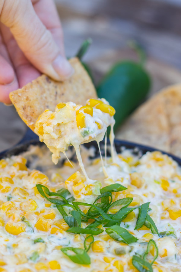 A tortilla chip dipped into the Hot Jalapeño Corn Dip.