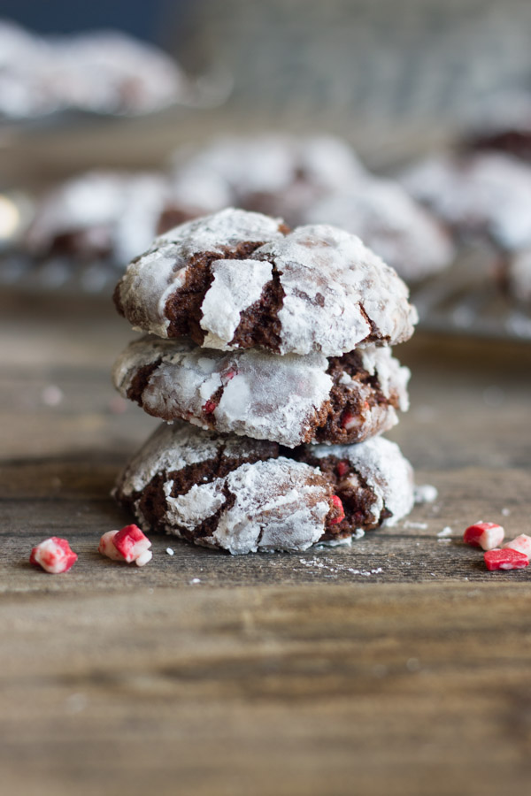 Peppermint Crunch Chocolate Crinkle Cookies stacked in a pile of three with bits of peppermint next to it.