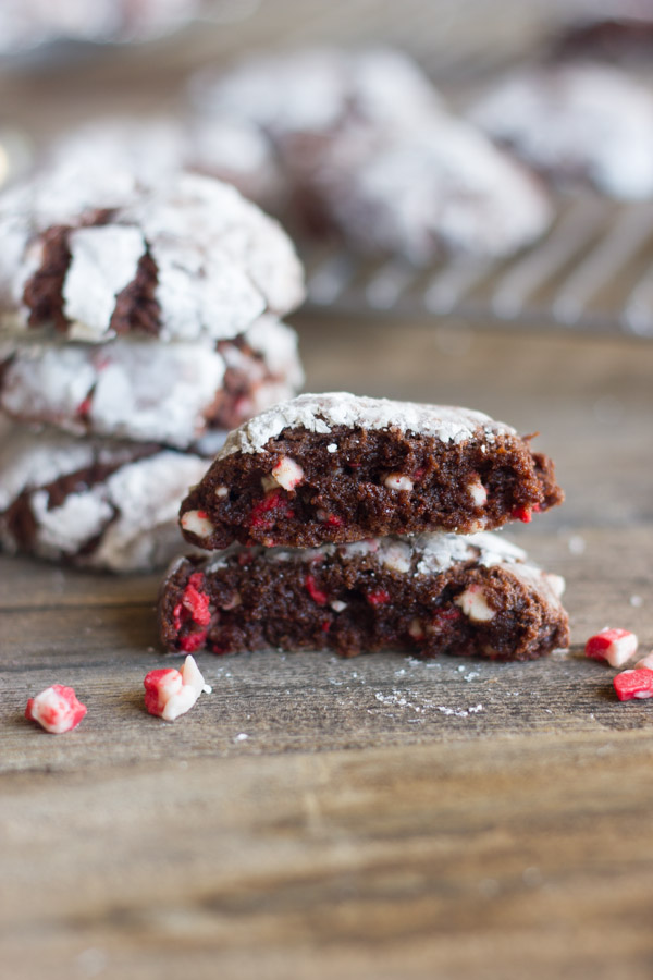 Peppermint Crunch Chocolate Crinkle Cookie cut in half and stacked with bits of peppermint next to it on a board.