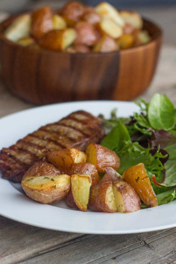 Roasted Red Potatoes on a dinner plate with steak and salad.