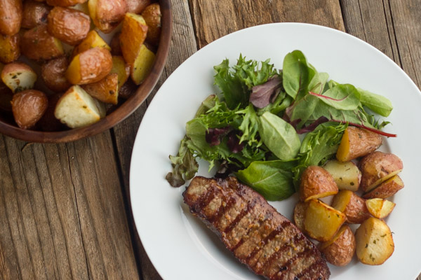 Roasted Red Potatoes on a dinner plate with steak and salad, next to a serving bowl with Roasted Red Potatoes in it.