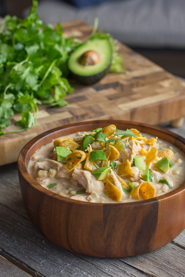 Creamy Crockpot White Chicken Chili in a bowl topped with Fritos, shredded cheese, avocado, and cilantro. There is also a cutting board with cilantro and half of an avocado in the background.
