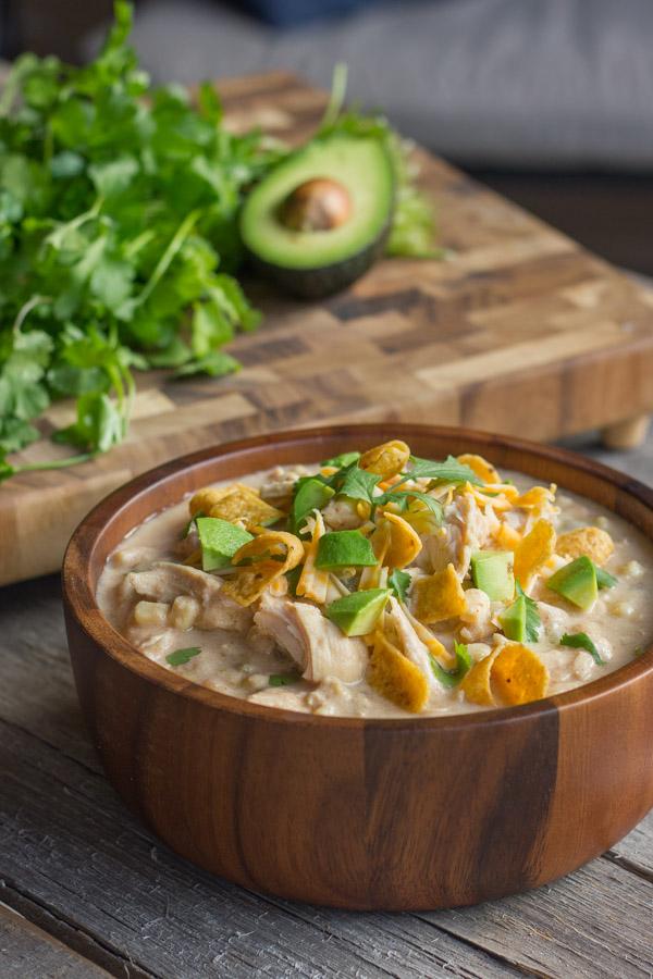 A wooden bowl of Creamy Crockpot White Chicken Chili with fritos, avocado, and cilantro.