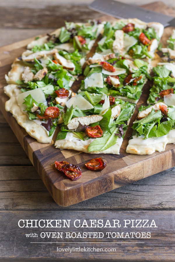Chicken Caesar Pizza With Oven Roasted Tomatoes sliced on a cutting board.