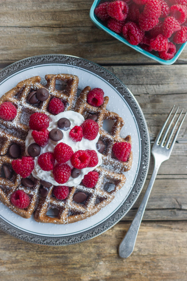 Chocolate Waffles With Fresh Raspberries, topped also with whipped cream and chocolate chips, on a plate with a fork next to it along with a carton of fresh raspberries.