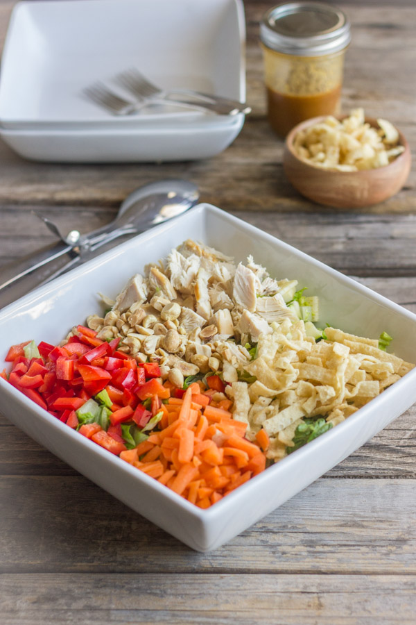 Chopped Chinese Chicken Salad ingredients in a large bowl with a bowl of wonton strips and a jar of Sesame Peanut Dressing in the background, along with two bowls and forks.