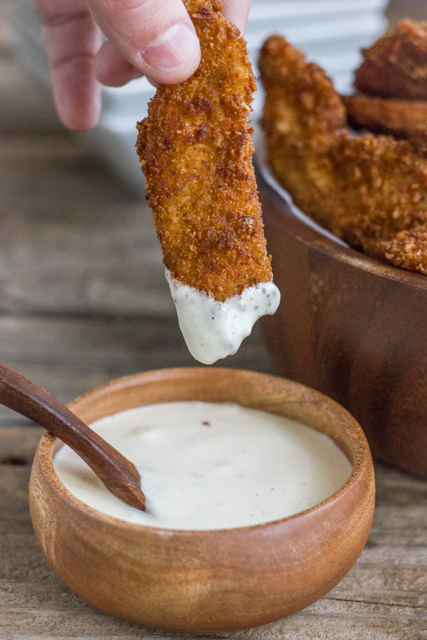 Extra Crispy Chicken Strip that has been dipped into a small bowl of dipping sauce.