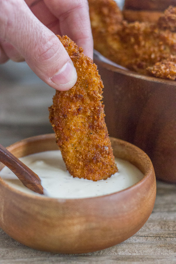 Extra Crispy Chicken Strip being dipped into a small bowl of dipping sauce.