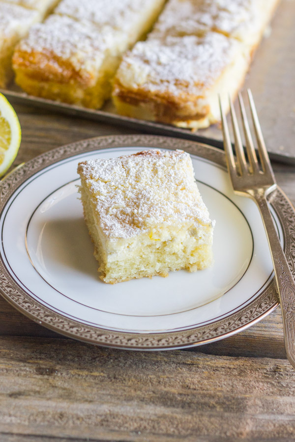 Greek Yogurt Cream Cheese Lemon Coffee Cake square piece on a plate with a fork, and more sliced cake on a serving tray in the background.