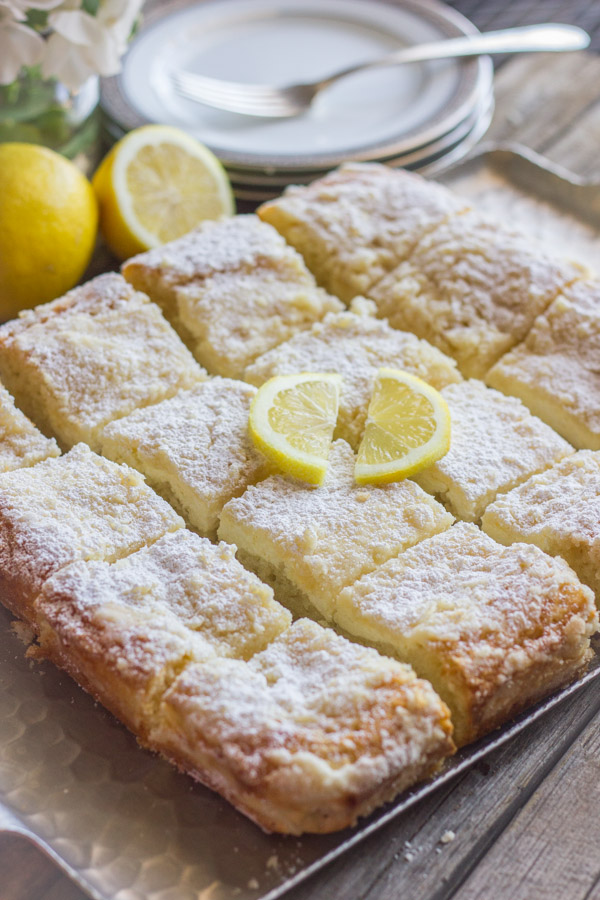 Greek Yogurt Cream Cheese Lemon Coffee Cake cut in squares on a serving tray with two slices of lemon on top for garnish.